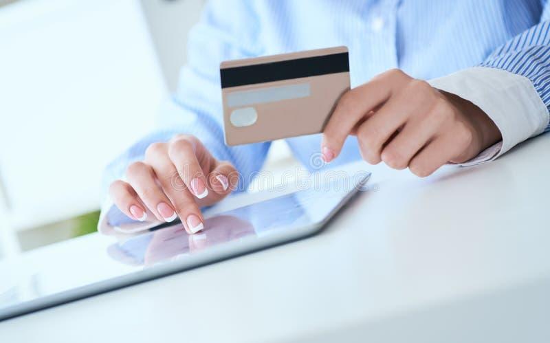 De handen die van de close-upvrouw ` s een creditcard houden en tabletpc voor online het winkelen met behulp van Middensectie jon stock foto