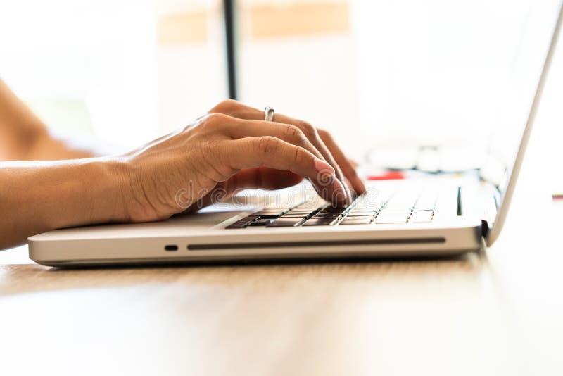 De handen die van de close-upvrouw ` s op laptop typen die op een houten bureau is royalty-vrije stock foto's