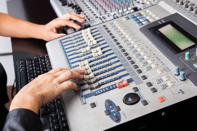 De Handen die van de beroeps aan Audiomixer binnen werken stock afbeeldingen