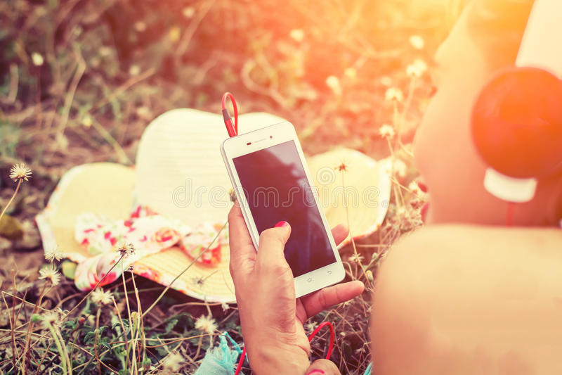 De handen die van de close-upvrouw smartphone gebruiken aan het luisteren muziek het leggen royalty-vrije stock afbeelding