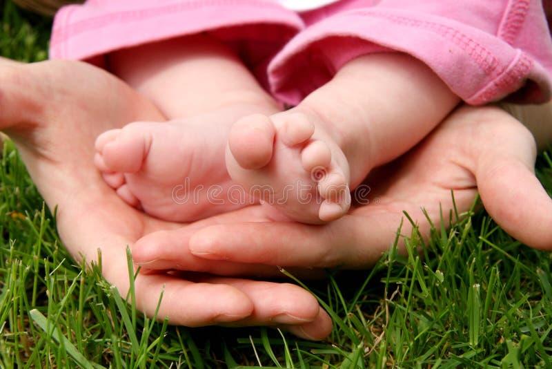 De handen die van de moeder haar zuigeling wiegen royalty-vrije stock foto