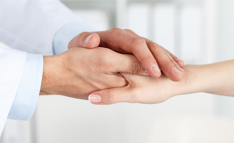 De handen die van de vriendschappelijke mannelijke arts de hand van de vrouwelijke patiënt houden royalty-vrije stock foto