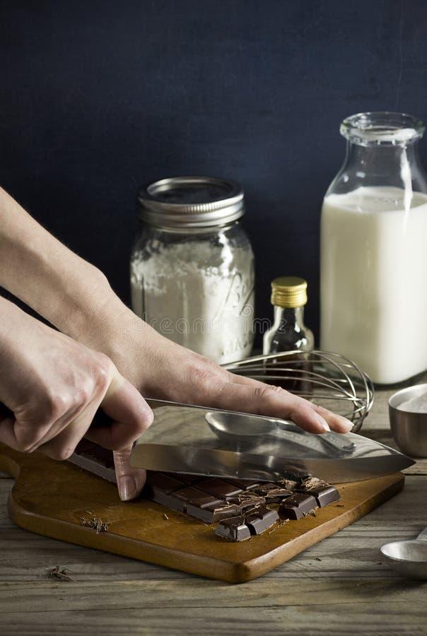 De Handen die van de vrouw Chocoladereep met Mes hakken royalty-vrije stock foto's