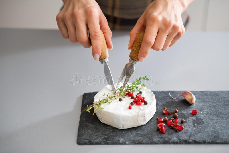 De handen die van de vrouw kaasmes en vork gebruiken om Camembert te snijden royalty-vrije stock foto's