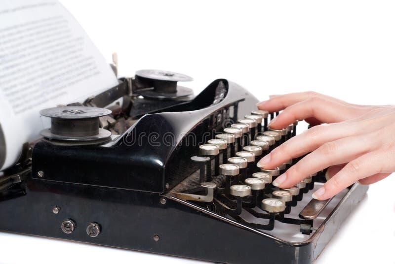 De handen die van de vrouw op uitstekende geïsoleerded schrijfmachine typen stock foto