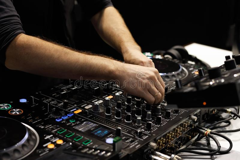 De handen die van DJ sporen op correct mixercontrolemechanisme mengen stock afbeelding