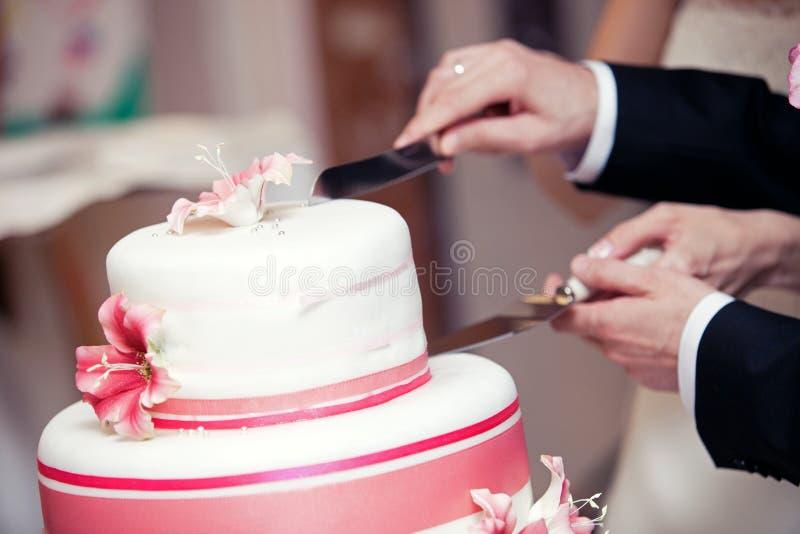 De handen die van het huwelijkspaar een huwelijkscake snijden stock foto's