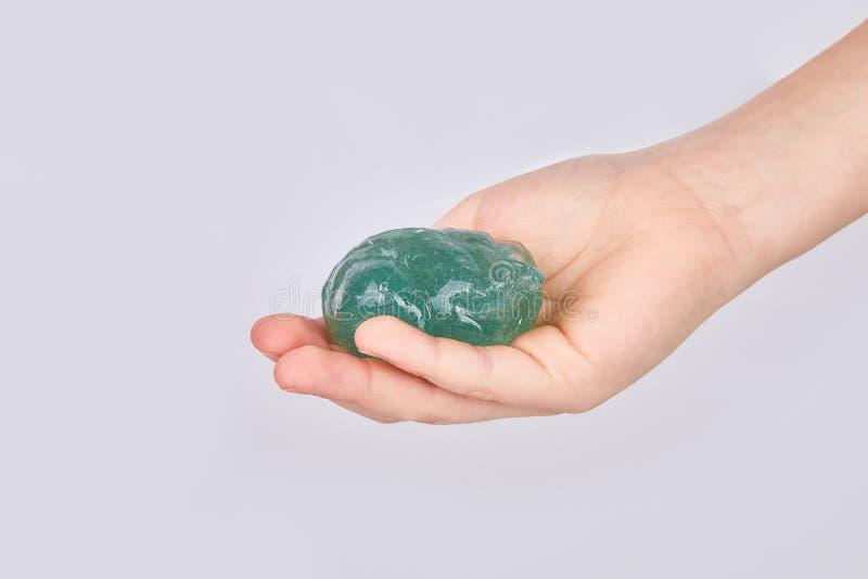 De handen die van het jonge geitje een transparant groen slijm geïsoleerd houden royalty-vrije stock afbeelding