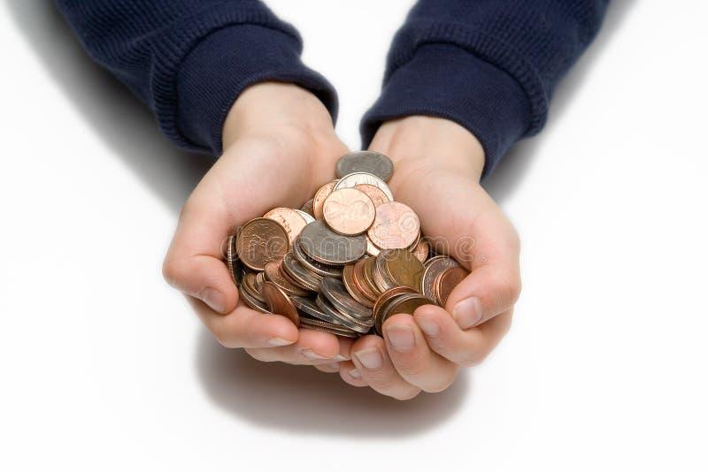 De handen die van het kind muntstukken houden stock foto
