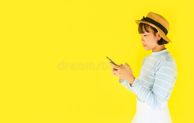 De handen die van het kindmeisje smartphone op gele achtergrond houden - Aziatische jonge vrouw die mobiele telefoonmanier vrij i royalty-vrije stock afbeeldingen