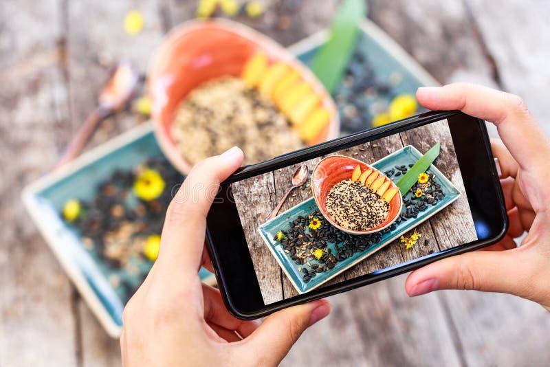 De handen die van het meisje foto van havermeelhavermoutpap nemen met zonnebloemzaden, sesam en perziken door smartphone stock fotografie
