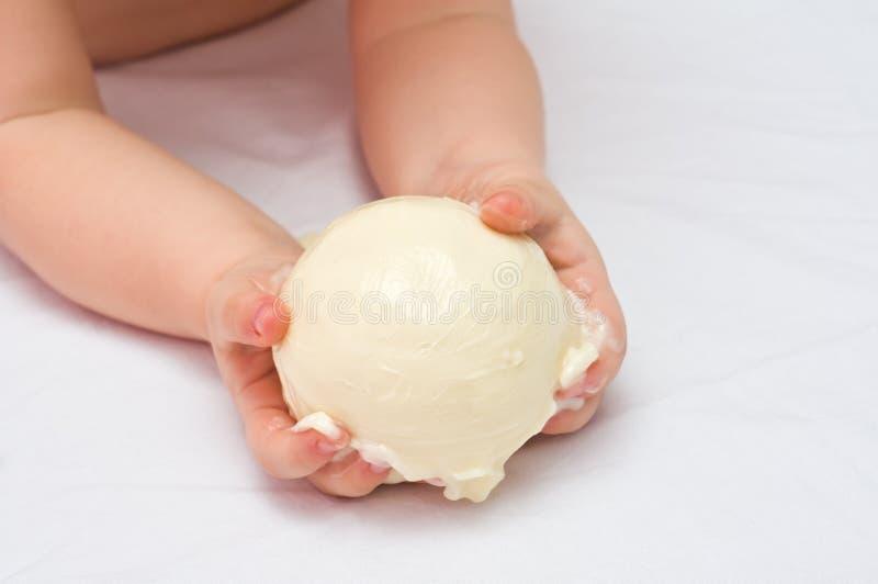De handen die van kinderen zachte boter houden stock afbeelding