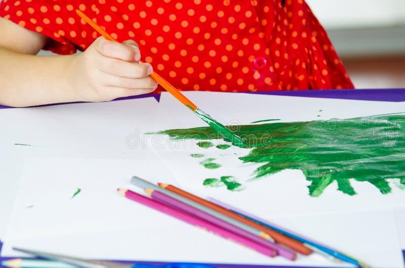 De handen die van meisjes verfborstel het schilderen houden royalty-vrije stock afbeeldingen