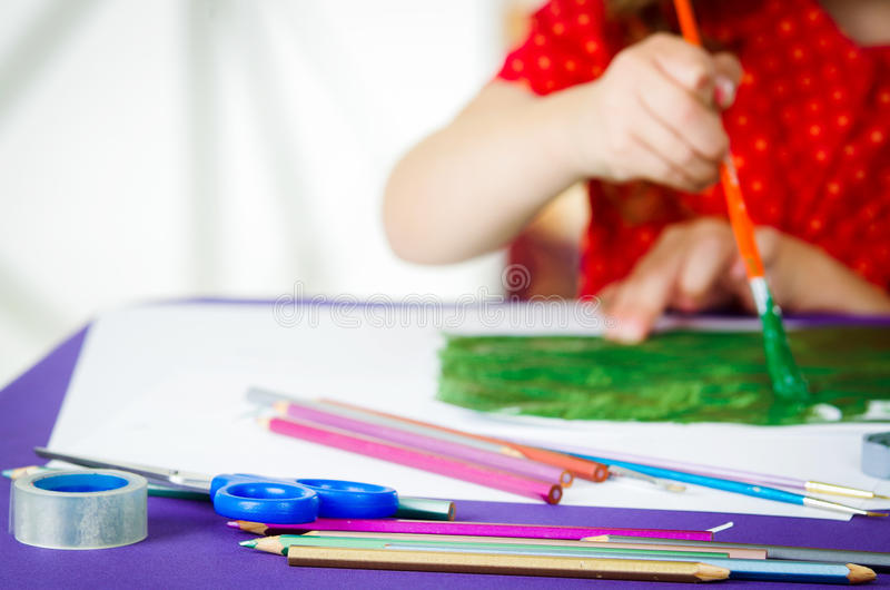 De handen die van meisjes verfborstel het schilderen houden stock afbeeldingen