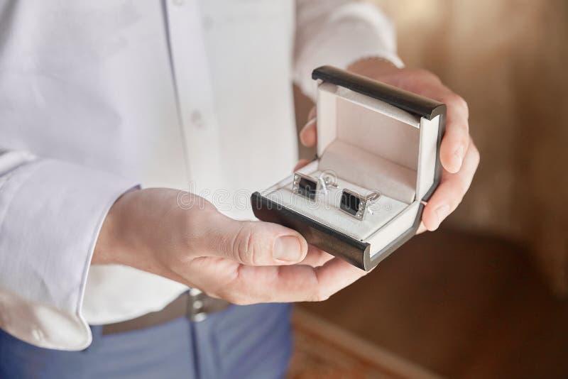 De handen die van mensen een doos met cufflinks houden stock foto's