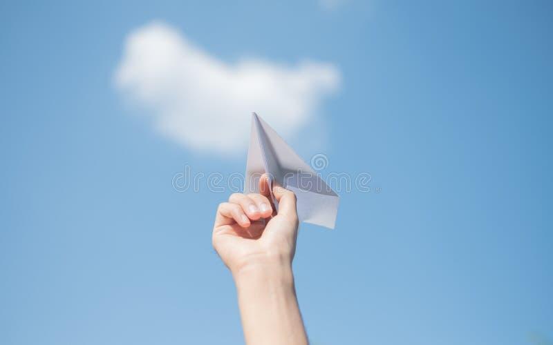 De handen die van mensen een Witboekraket met een heldere blauwe achtergrond houden stock foto's
