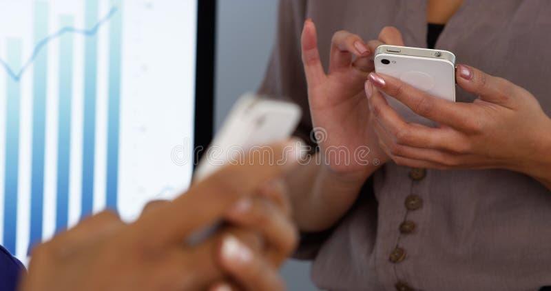 De handen die van onderneemstersvrouwen aan mobiele telefoons werken stock afbeeldingen