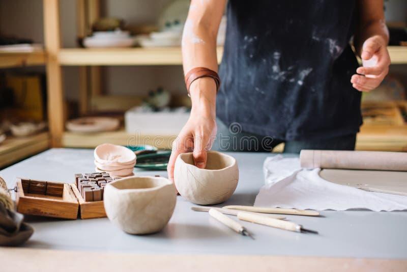 De handen die van de de pottenbakkersvakman van het aardewerkvakmanschap rode klei werken royalty-vrije stock foto