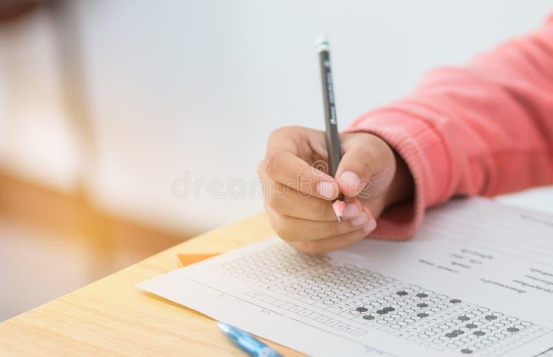 De handen die van schoolstudenten examens nemen, schrijvend het verstand van de onderzoeksruimte stock foto's