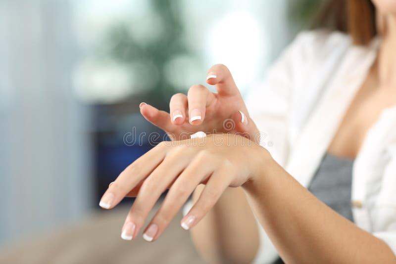 De handen die van de schoonheidsvrouw met vochtinbrengende crèmeroom hydrateren royalty-vrije stock afbeelding