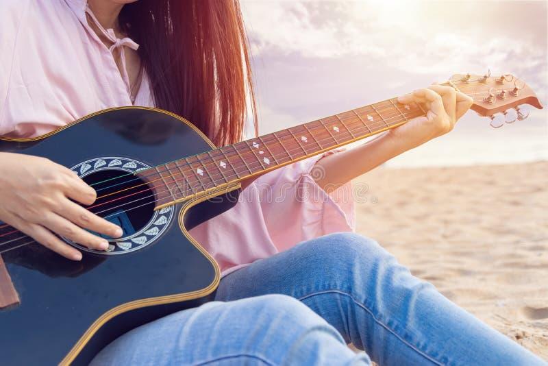 De handen die van de vrouw akoestische gitaar spelen, vangen snaren door vinger op zandig strand in zonsondergangtijd Speelmuziek royalty-vrije stock foto's