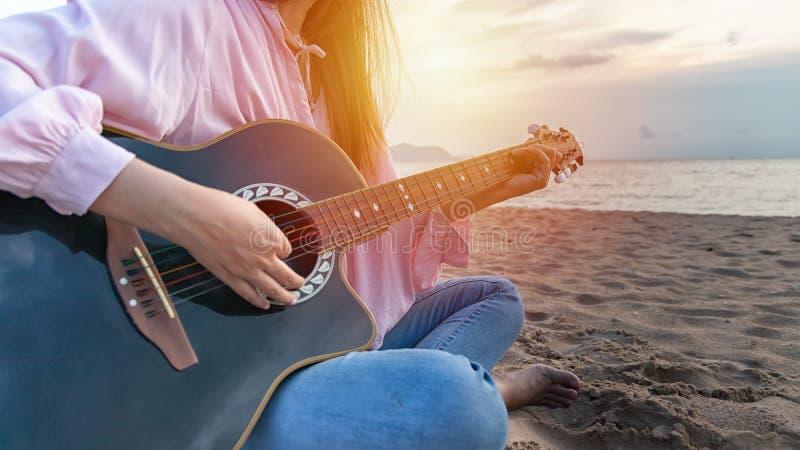 De handen die van de vrouw akoestische gitaar spelen, vangen snaren door vinger op zandig strand in zonsondergangtijd Speelmuziek stock foto