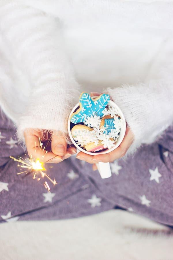 De handen die van de vrouw een kop met de winter/Kerstmiskoekjes houden; de winterachtergrond met exemplaarruimte stock afbeelding