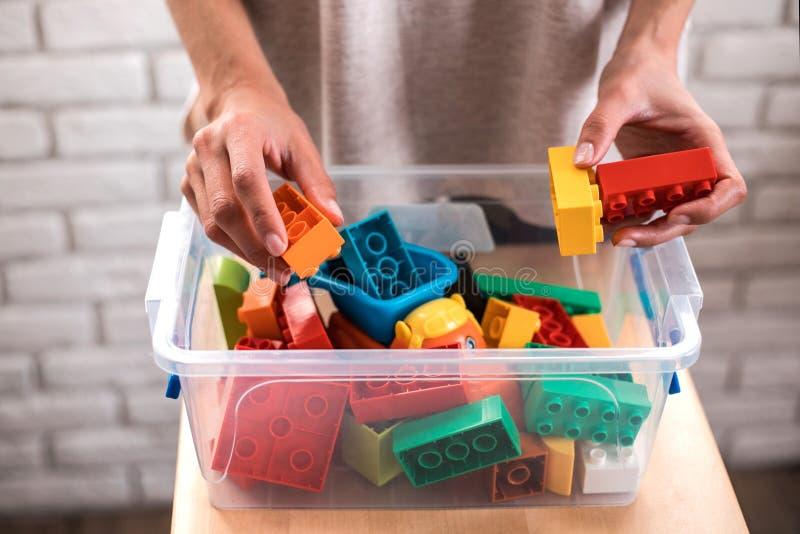 De handen die van de vrouw gekleurde blokken zetten in doos stock afbeeldingen