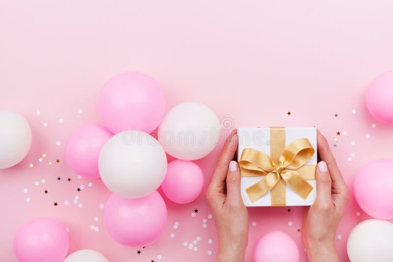 De handen die van de vrouw gift of huidig vakje op roze pastelkleurlijst verfraaide ballons en confettien houden Vlak leg samenst royalty-vrije stock foto