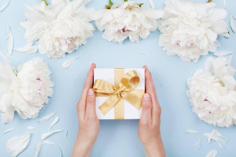 De handen die van de vrouw gift of huidig vakje verfraaide witte pioenbloemen op de bovenkantmening van de pastelkleurlijst geven stock afbeeldingen