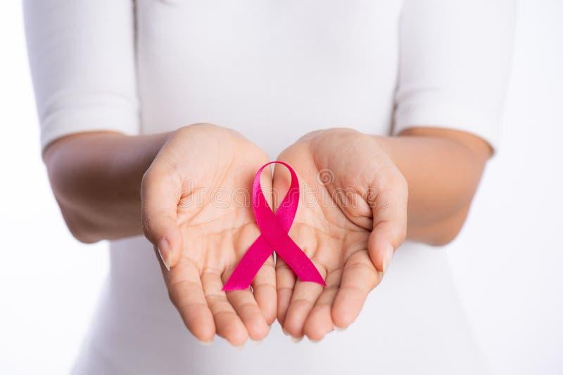 De handen die van de vrouw roze de voorlichtingslint van borstkanker op witte achtergrond houden Gezondheidszorg en geneeskundeco stock foto
