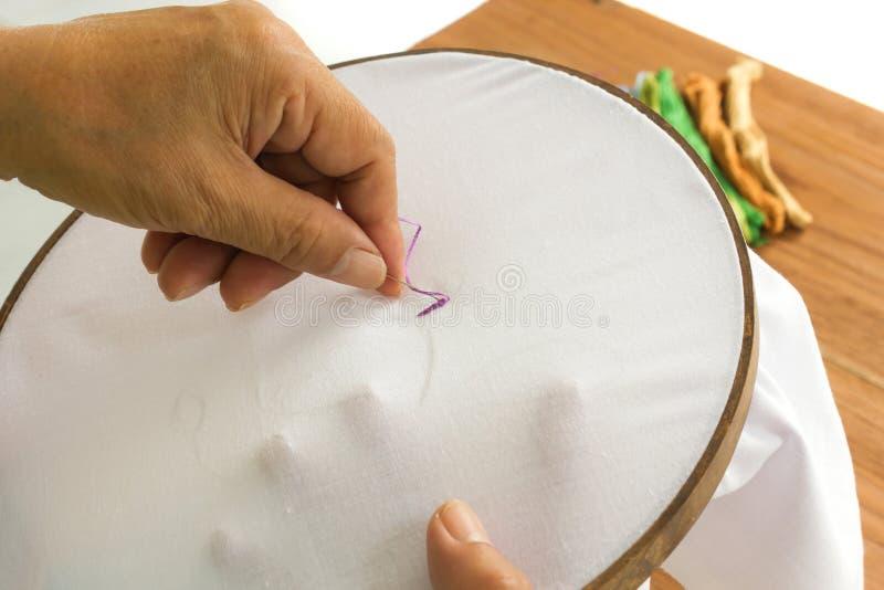 De handen die van vrouwen een bloem op een witte katoenen stof borduren royalty-vrije stock foto's