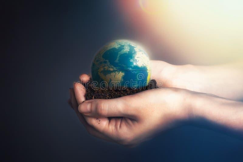 De handen die van vrouwen grond met een bol van de aarde houden Het concept milieubehoud, biologische landbouw licht royalty-vrije stock afbeelding