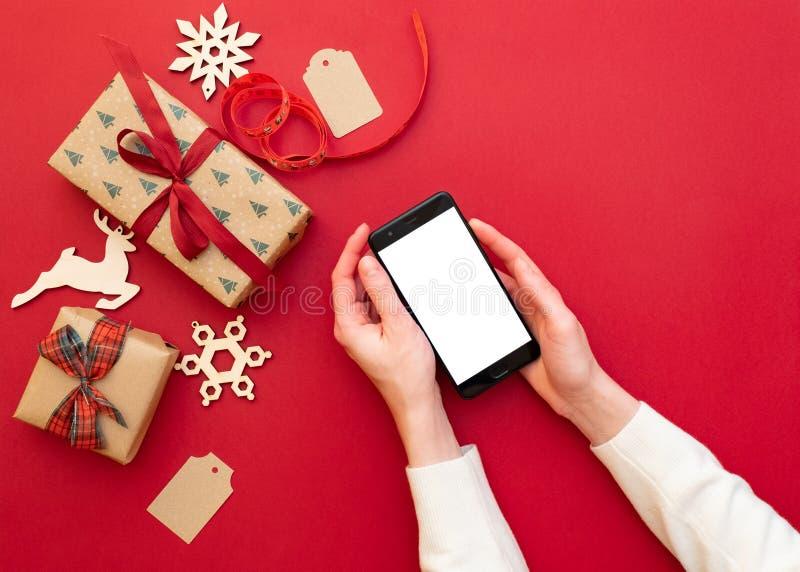 de handen die van vrouwen telefoon op rode achtergrond met Kerstmisdecoratie en giften houden Kerstmis en Gelukkige Nieuwjaarsame royalty-vrije stock fotografie