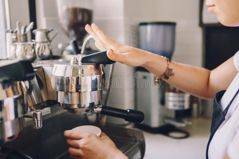 De handen die van vrouwenbarista gietende koffie van koffiemachine maken in plastic transparante kop stock afbeeldingen