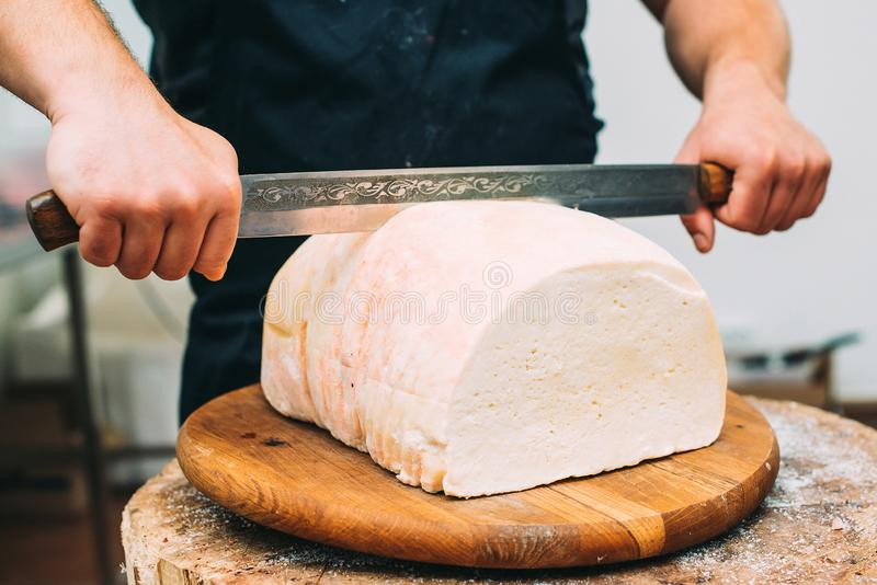 De handen die van de winkelier een hoofd van witte kaas snijden De scherpe kaas, sluit omhoog Artisanale kaas in een straatmarkt  stock fotografie