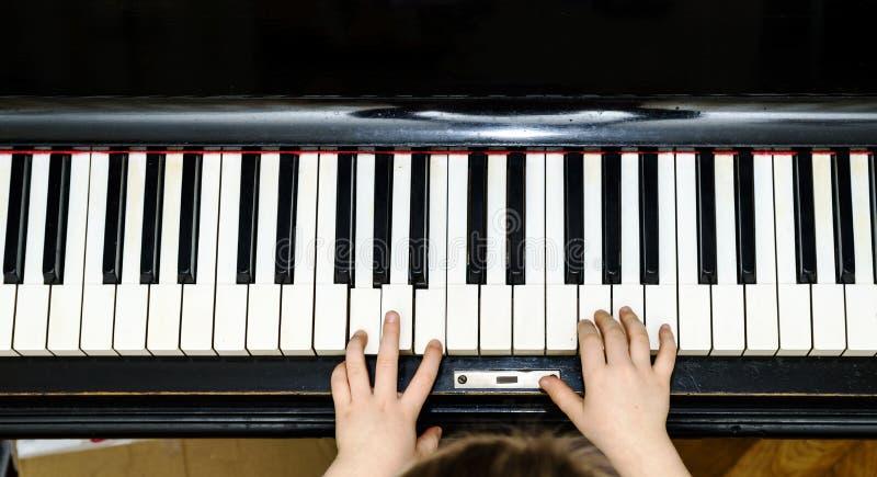 De handen en de piano de mening van het toetsenbordclose-up van het meisje stock fotografie