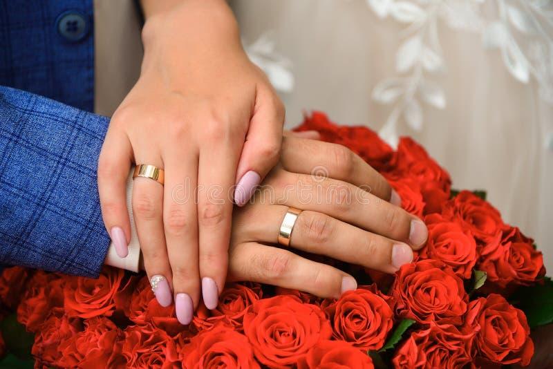 De handen en de ringen op huwelijksboeket van rode rozen sluiten omhoog royalty-vrije stock foto