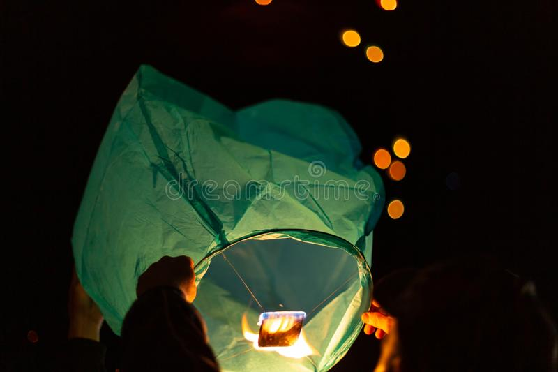 De handen houden een groene drijvende lantaarn tegen aangezien zij voorbereidingen treffen om het vrij te geven om in de hemel me royalty-vrije stock foto