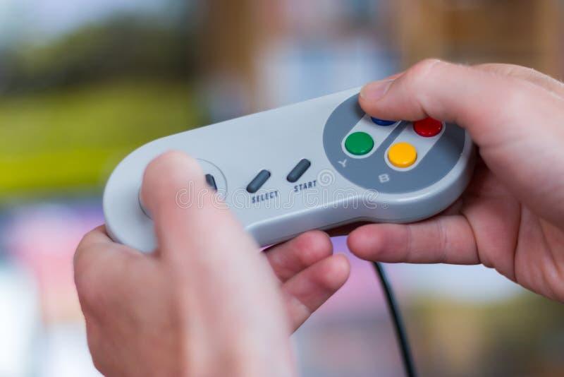De handen houden een retro videospelletjecontrolemechanisme en spelen, onscherpe achtergrond royalty-vrije stock foto