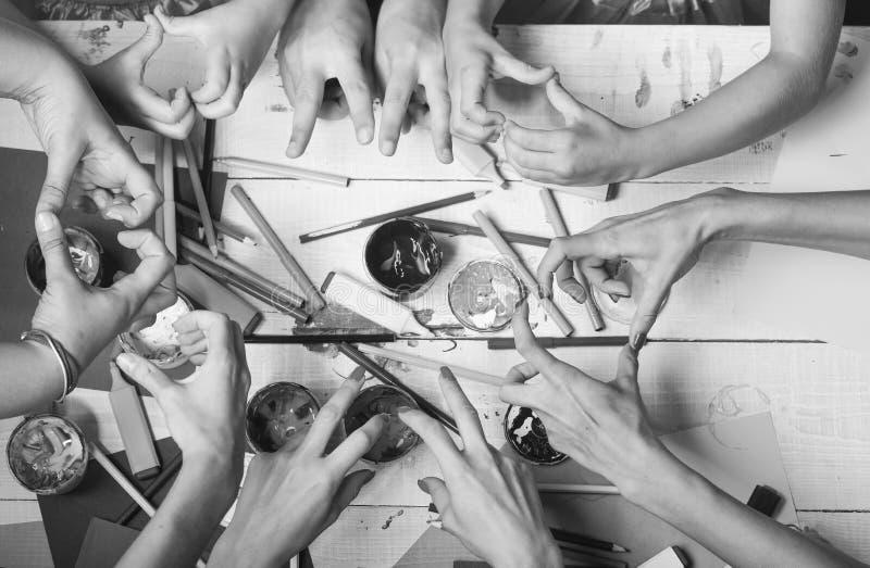 De handen houden kleurrijke tellers, potloden en verven Kunst en ambachtconcept Kunstenaarshanden met kantoorbehoeften en documen stock afbeeldingen