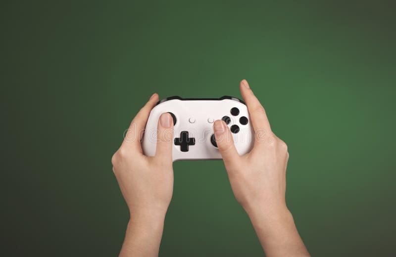 De handen houden witte gamepad tegen een groene achtergrond royalty-vrije stock fotografie