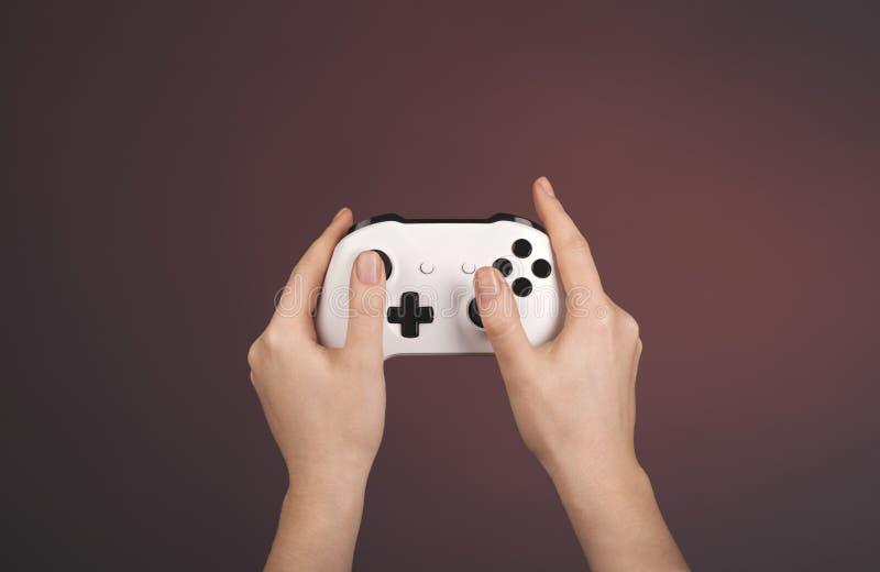 De handen houden witte gamepad tegen een rode achtergrond stock afbeeldingen