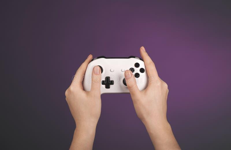 De handen houden witte gamepad tegen een violette achtergrond royalty-vrije stock afbeeldingen