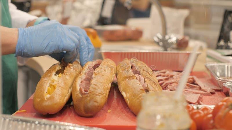 De handen koken het zetten van stukkenworst in besnoeiing op baguette in snel voedselkoffie stock foto's