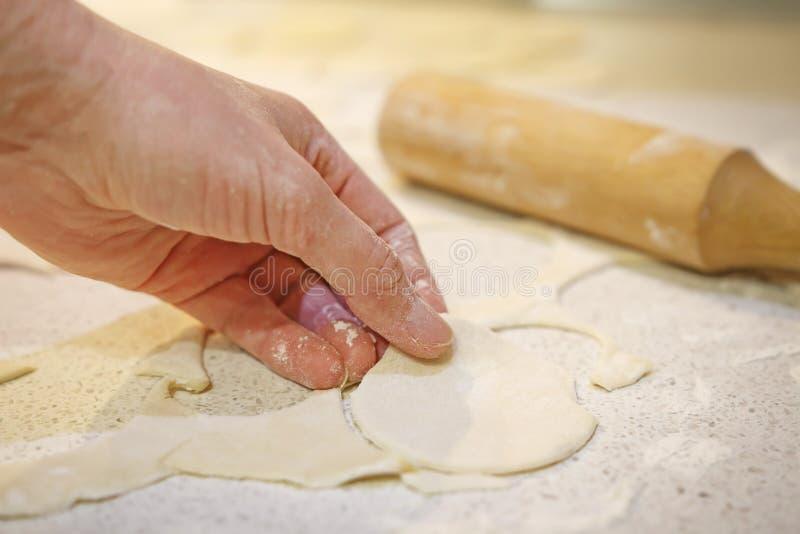De handen maken beeldjes voor bakselkoekjes van deeg Bloem, deegrol op lijst met deeg De producten van de gebakjebakkerij royalty-vrije stock foto