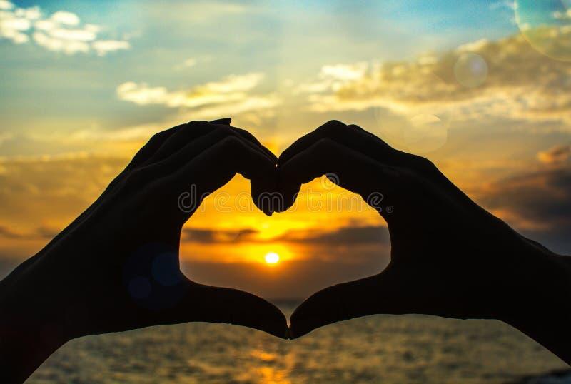 De handen maken hart bij zonsondergang royalty-vrije stock afbeelding