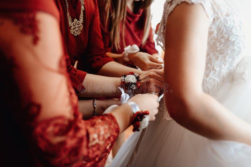 De handen maken het korset aan de bruid vast stock fotografie