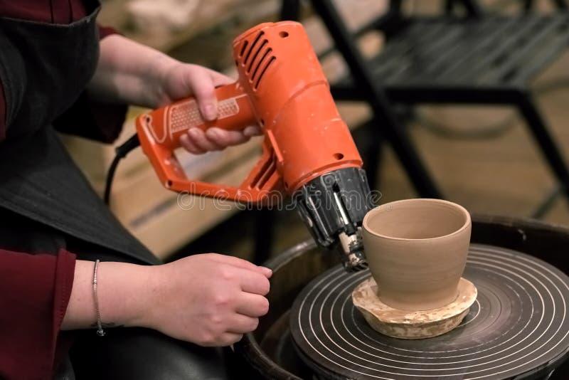 De handen met een droogkap drogen een kleikop op een wiel van de pottenbakker royalty-vrije stock foto's