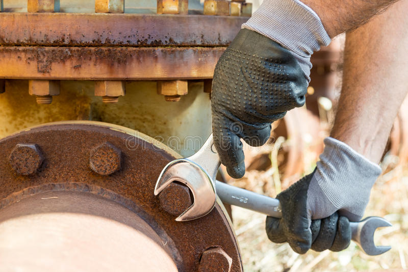 De handen met het Werkhandschoenen die een Moersleutel houden en halen zeer Rusty Bolts aan stock afbeeldingen